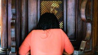 Fotografía de archivo de una mujer arrodillada confesándose ante un sacerdote.