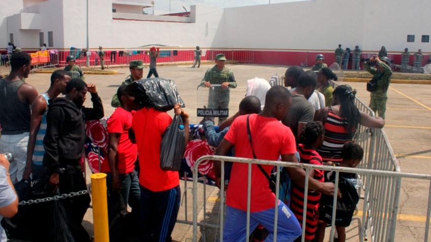 Migrantes esperan afuera de una estación en Chiapas