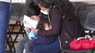 Foto de madre abrazando a sus dos pequeños mientras lee un documento.