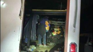 Imagen de migrantes, que están de espaldas, que viajaban hacinados en un camión