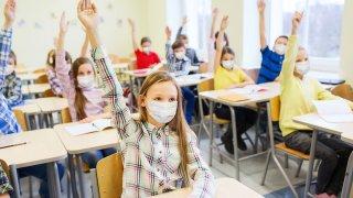 estudiantes alzando la mano con mascarillas puestas.