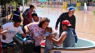 Varios hombres trasladan en lancha a una mujer y a un bebé en medio de una inundación